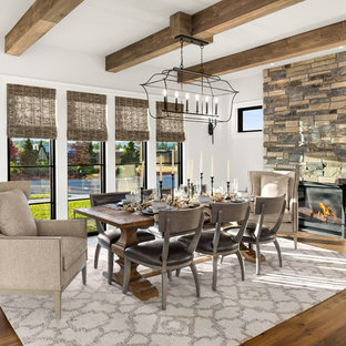 Enclosed dining room - large cottage medium tone wood floor and brown floor enclosed dining room idea in Portland with white walls, a standard fireplace and a stone fireplace