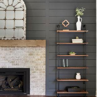 Diseño de comedor de cocina de estilo de casa de campo, de tamaño medio, con paredes negras, suelo de madera en tonos medios, chimenea tradicional, marco de chimenea de ladrillo y suelo marrón
