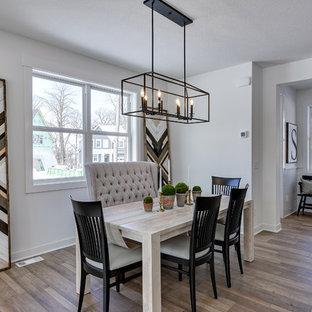Réalisation d'une salle à manger champêtre de taille moyenne avec un mur blanc, sol en stratifié, une cheminée standard, un manteau de cheminée en carrelage et un sol gris.