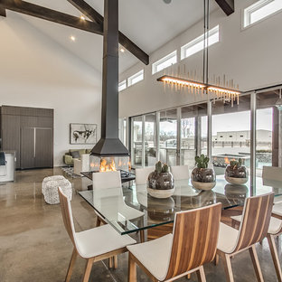 Example of a trendy concrete floor great room design in Oklahoma City with gray walls and a hanging fireplace