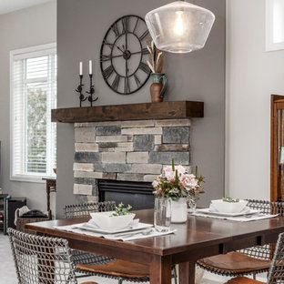 Kitchen/dining room combo - mid-sized farmhouse carpeted and gray floor kitchen/dining room combo idea in Portland with gray walls, a standard fireplace and a stone fireplace