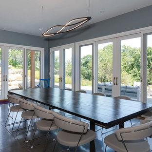 Immagine di una sala da pranzo aperta verso il soggiorno industriale di medie dimensioni con pavimento in cemento, pavimento grigio e pareti blu
