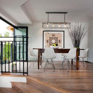 Exemple d'une grande salle à manger tendance fermée avec un mur blanc, un sol en bois clair, aucune cheminée et un sol marron.