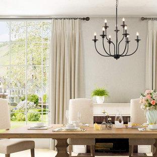 Immagine di una piccola sala da pranzo aperta verso la cucina minimalista con pareti bianche, pavimento in compensato, camino ad angolo, cornice del camino in legno e pavimento marrone