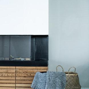 Inspiration pour une salle à manger avec un mur gris, un sol en carrelage de porcelaine, une cheminée ribbon et un manteau de cheminée en lambris de bois.