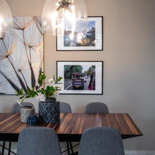 Immagine di una sala da pranzo con pareti grigie, pavimento in gres porcellanato, camino lineare Ribbon e cornice del camino in perlinato