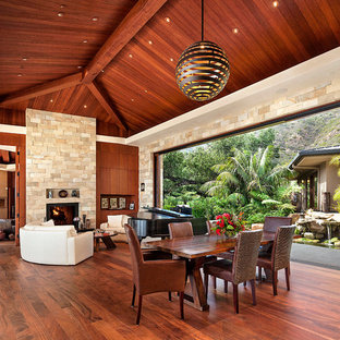 Idee per un'ampia sala da pranzo tropicale con pareti beige, parquet scuro, cornice del camino in pietra e camino classico
