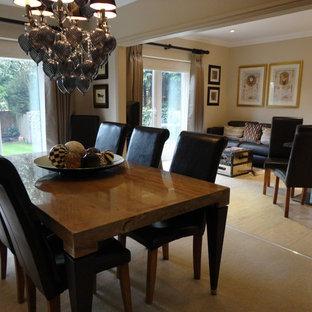 Esempio di una sala da pranzo aperta verso il soggiorno moderna di medie dimensioni con pareti beige, moquette, camino classico, cornice del camino in pietra e pavimento beige
