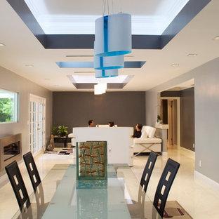 Modelo de comedor moderno, grande, abierto, con paredes azules, suelo de mármol, chimenea lineal y marco de chimenea de metal