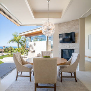 Medium sized coastal kitchen/dining room in Los Angeles with white walls, travertine flooring, a standard fireplace, a stone fireplace surround and white floors.