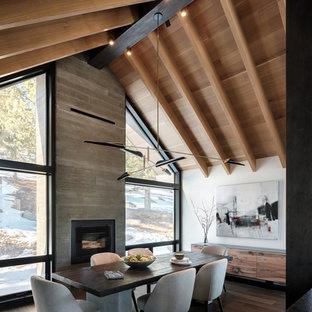 Idée de décoration pour une salle à manger ouverte sur la cuisine chalet de taille moyenne avec un mur blanc, un sol en bois brun, une cheminée standard et un manteau de cheminée en béton.