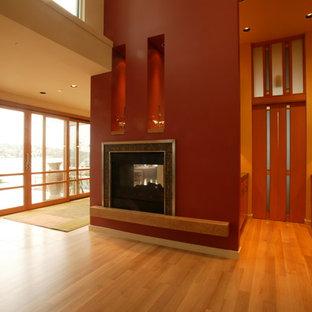 シアトルのコンテンポラリースタイルのおしゃれなダイニング (両方向型暖炉、石材の暖炉まわり、赤い壁) の写真