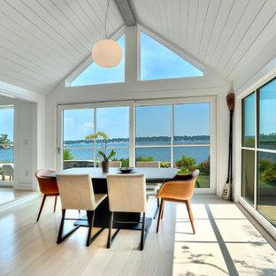 Imagen de comedor minimalista, de tamaño medio, abierto, con paredes blancas, suelo de madera clara, chimenea de esquina, marco de chimenea de ladrillo y suelo beige