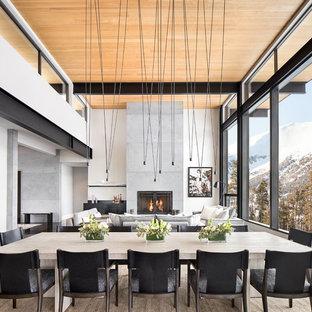 Foto di una sala da pranzo aperta verso il soggiorno design con pareti beige, camino lineare Ribbon e cornice del camino in metallo