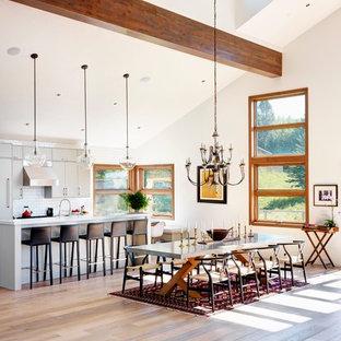 Foto på ett mycket stort lantligt kök med matplats, med vita väggar och ljust trägolv
