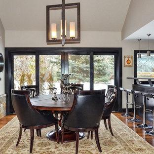 Ejemplo de comedor de cocina rústico, de tamaño medio, con paredes grises, suelo de madera en tonos medios, chimenea tradicional y marco de chimenea de piedra