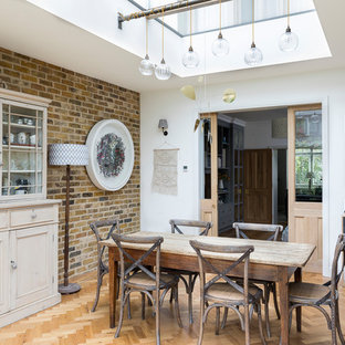 Inspiration for a medium sized eclectic dining room in London with white walls, light hardwood flooring and brown floors.