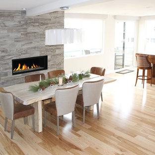 Ispirazione per una sala da pranzo aperta verso la cucina moderna di medie dimensioni con pareti bianche, parquet chiaro, camino lineare Ribbon e cornice del camino piastrellata