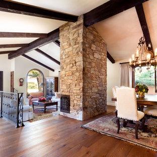 Идея дизайна: гостиная-столовая среднего размера в средиземноморском стиле с бежевыми стенами, паркетным полом среднего тона, угловым камином, фасадом камина из камня, коричневым полом и балками на потолке