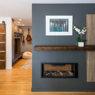 Идея дизайна: кухня-столовая среднего размера в современном стиле с серыми стенами, светлым паркетным полом, двусторонним камином, фасадом камина из штукатурки и коричневым полом