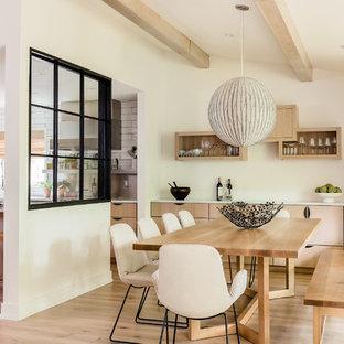 Réalisation d'une salle à manger ouverte sur la cuisine design avec un mur blanc, un sol en bois clair, un sol beige et un plafond en poutres apparentes.