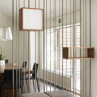Modelo de comedor minimalista con suelo de madera oscura y paredes metalizadas
