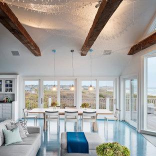 Imagen de comedor tradicional renovado, grande, abierto, con paredes blancas, suelo de cemento, suelo azul, estufa de leña y marco de chimenea de metal