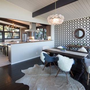 Foto di una sala da pranzo aperta verso la cucina moderna con parquet scuro e pareti multicolore