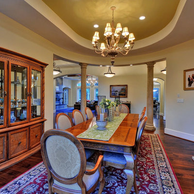 Example of a tuscan dark wood floor dining room design in San Francisco with beige walls and a standard fireplace