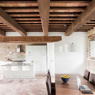 Cette image montre une grande salle à manger ouverte sur le salon méditerranéenne avec un mur blanc et un sol en brique.