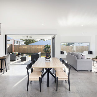 This is an example of a scandinavian open plan dining in Brisbane with white walls, concrete floors and brown floor.