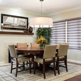 Ispirazione per una sala da pranzo tradizionale chiusa e di medie dimensioni con pareti beige, pavimento in bambù, camino classico e cornice del camino in pietra