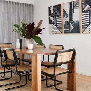This is an example of a mid-sized scandinavian dining room in Melbourne with white walls, light hardwood floors, no fireplace and brown floor.