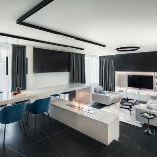 Immagine di una grande sala da pranzo aperta verso il soggiorno minimal con pareti bianche, cornice del camino piastrellata e pavimento nero