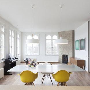 Ispirazione per una sala da pranzo aperta verso il soggiorno moderna con pareti bianche, pavimento in legno massello medio, stufa a legna, cornice del camino in mattoni e pavimento marrone
