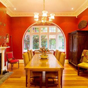 Immagine di una sala da pranzo classica con pareti rosse e camino classico