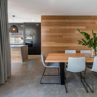 This is an example of a contemporary open plan dining in Brisbane with brown walls, concrete floors and grey floor.
