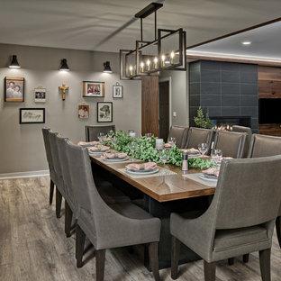 Idée de décoration pour une grande salle à manger ouverte sur le salon design avec un mur gris, un sol en vinyl, une cheminée standard, un manteau de cheminée en carrelage et un sol multicolore.