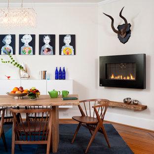 Modelo de comedor vintage, grande, abierto, con paredes blancas, suelo de madera en tonos medios, marco de chimenea de metal, chimenea lineal y suelo marrón