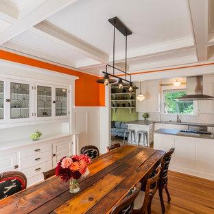 ポートランドのコンテンポラリースタイルのおしゃれなダイニングキッチン (オレンジの壁、無垢フローリング、暖炉なし、茶色い床) の写真