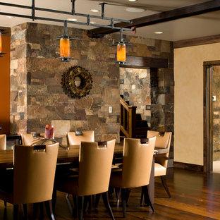 Inspiration pour une salle à manger ouverte sur le salon chalet de taille moyenne avec un mur orange et un sol en bois brun.