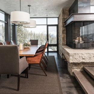他の地域の巨大なコンテンポラリースタイルのおしゃれなダイニング (ベージュの壁、コンクリートの床、両方向型暖炉、石材の暖炉まわり) の写真