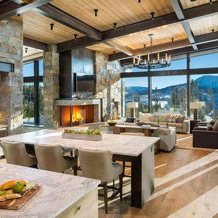 Cette image montre une grand salle à manger ouverte sur le salon chalet avec un sol en bois brun, un manteau de cheminée en pierre, un sol marron et une cheminée d'angle.