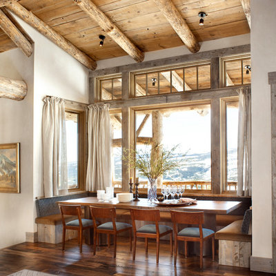 Example of a mid-sized mountain style dark wood floor and brown floor kitchen/dining room combo design in Other with white walls