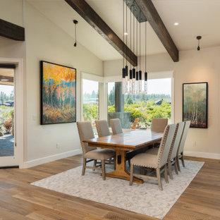 Foto di una sala da pranzo aperta verso la cucina rustica di medie dimensioni con pareti bianche, pavimento in legno massello medio, pavimento marrone e travi a vista