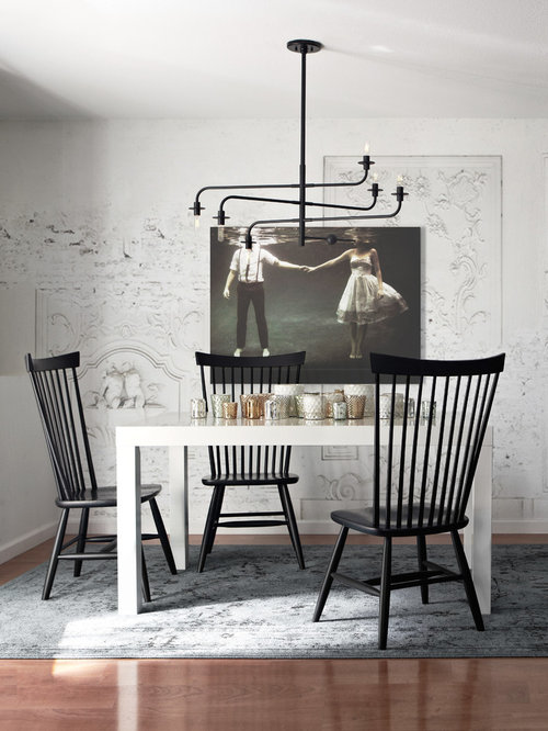 example of a danish dining room design in san francisco with white walls and dark hardwood