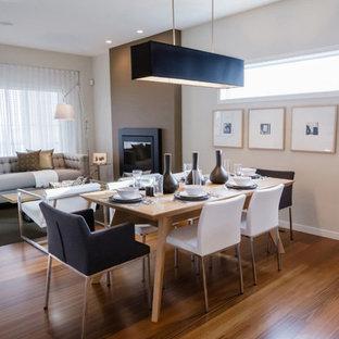 Modelo de comedor contemporáneo, de tamaño medio, abierto, con paredes beige, suelo de madera en tonos medios, chimeneas suspendidas, marco de chimenea de yeso y suelo marrón