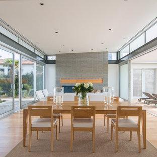 Неиссякаемый источник вдохновения для домашнего уюта: большая кухня-столовая в стиле модернизм с белыми стенами, паркетным полом среднего тона, стандартным камином и фасадом камина из бетона
