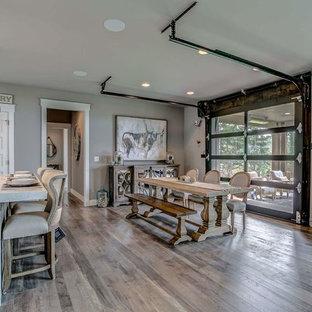 Immagine di una sala da pranzo aperta verso il soggiorno country di medie dimensioni con pareti grigie, pavimento in laminato e pavimento grigio