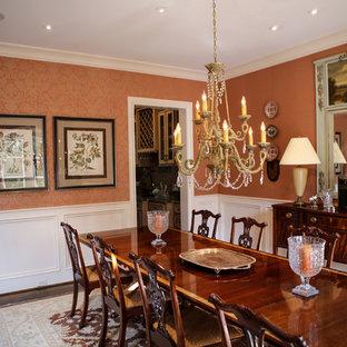 Foto di un'ampia sala da pranzo classica chiusa con parquet scuro e pareti arancioni